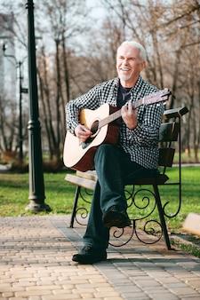 Повысьте свои навыки. низкий угол веселого зрелого мужчины, настраивающего и играющего на гитаре