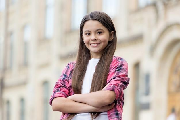 소녀의 자신감을 높여줍니다. 자신감 있는 아이는 야외에서 팔짱을 끼고 있습니다. 패션 소녀의 자신감 있는 모습. 캐주얼 스타일. 여름 트렌드. 트렌디한 아동복. 어린이용 옷장. 매일 위대해지세요.