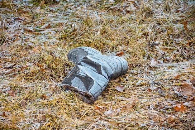 冷ややかな草、放棄されたブーツ、失われた靴でブーツ