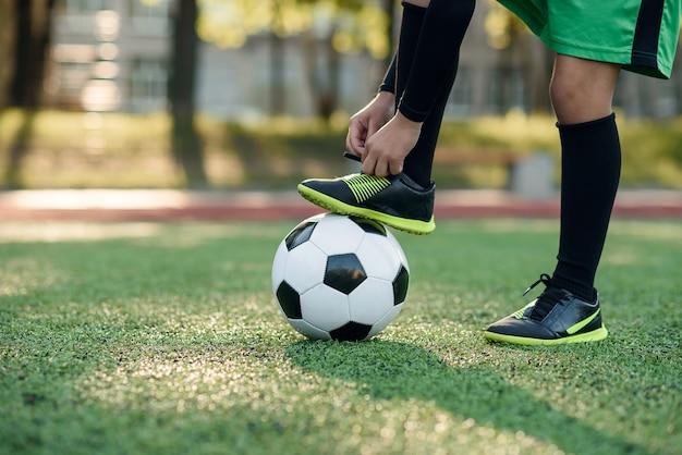 ボールの上のサッカー選手のブーツ。サッカースタジアムで靴ひもを結ぶ少年。