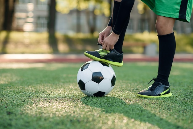 Boot of soccer player on a ball. boy tying shoelace on soccer stadium.
