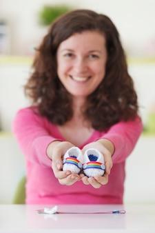ゲイ産科家族の赤ちゃんbooteesを保持している陽気な女性