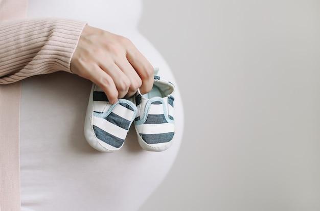 임신 한 배를 가진 미래의 어머니의 손에있는 옷