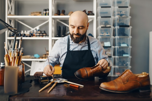 Bootmaker with brush tints shoes, footwear repair service. craftsman skill, shoemaking workshop, master works with boots