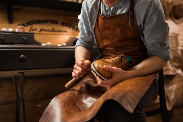 Bootmaker in workshop making shoes
