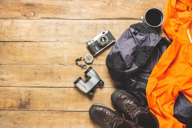 トレイル、ジャケット、バックパック、木製の背景にハイキング用品のブーツ。ハイキング、観光、キャンプ、山、森のコンセプトです。バナー。フラット横たわっていた、トップビュー