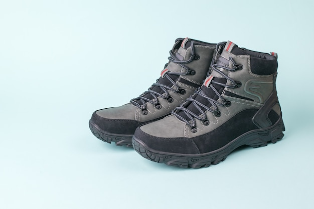 Boots for hiking in cold weather on a blue background. men's shoes for cold weather. casual sports men's shoes.