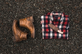 Boots near shirt and knife