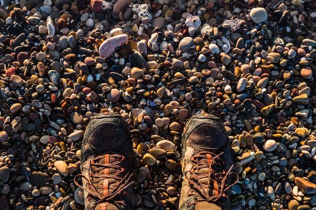ビーチの小石の上に立って、地面に向かっているハイカーのブーツ。