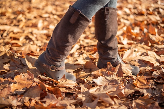 秋の落ち葉を歩く女性のブーツ
