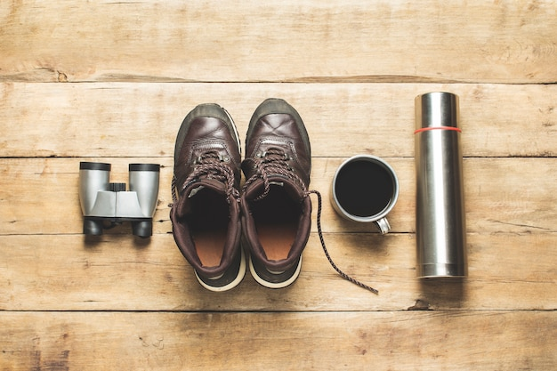 Boots for trail, binoculars, thermos, cup with tea on a wooden background. concept of hiking, tourism, camp, mountains, forest.