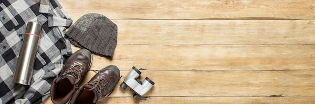 Boots for a trail, shirt, hat, binoculars on a wooden background. concept of hiking, tourism, camp, mountains, forest.