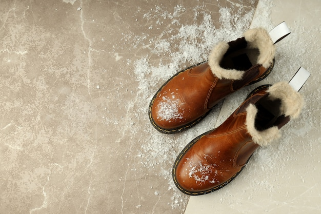 Boots with snow on two tone background.