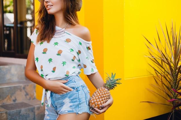 Попа и бедра в джинсовых шортах привлекательной женщины на летних каникулах, стройная фигура, сексуальное тело, держит ананас, фруктовая диета, детокс, загорелая кожа, желтый фон