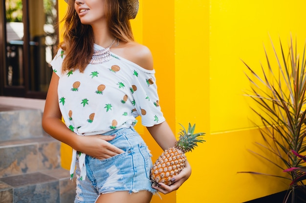 Booty and hips in jeans shorts of attractive woman on summer vacation, skinny figure sexy body, holding pineapple, fruit diet detox, tanned skin, yellow background