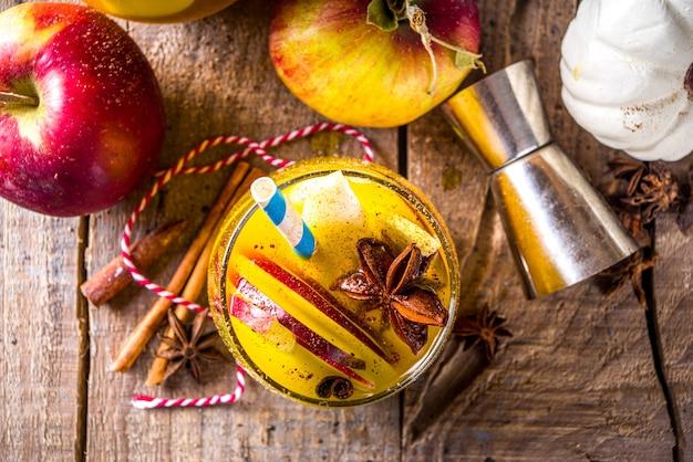 かぼちゃのパンプキンパーティーパンチ、かぼちゃジュース、リンゴ、梨、スパイスの感謝祭のサングリア、暖かいセーターと食材のコピースペースと居心地の良い木製の背景