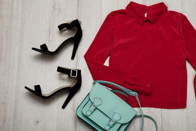 Bordeaux blouse, black shoes, handbag. fashionable concept. wooden background