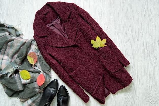 Пальто бордо, шарф, черные сапоги и осенние листья