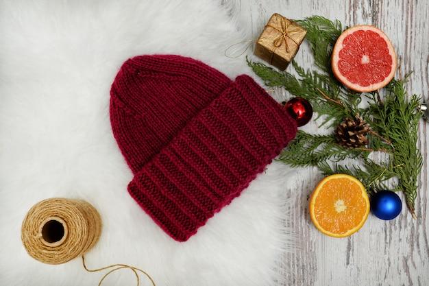 ボルドーハット、スプルースの枝、クリスマスツリーの飾り、柑橘類。新年のコンセプトです。
