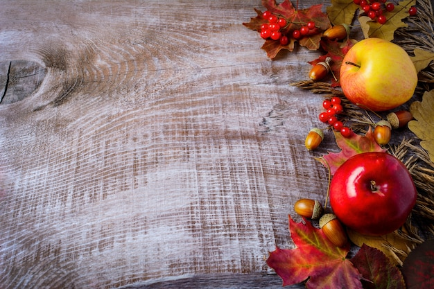 Border of apples, berries and fall leaves on the rustic wooden