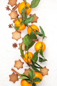 Border of christmas star cookies with spices and mandarin on white background with copyspace. top view