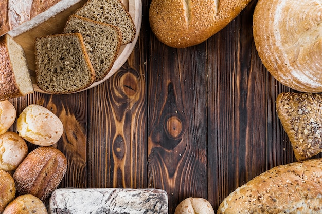 Border of different baked breads on the wooden backdrop