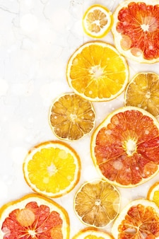 Border of dried slices of various citrus fruits on white background. many orange lemon grapefruit with copyspace. toned bokeh and snow