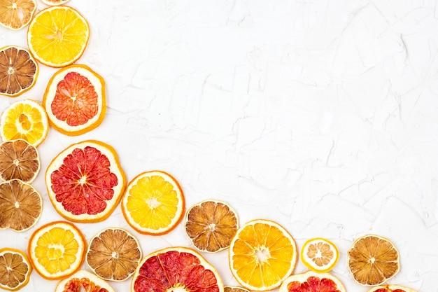 Border of dried slices of various citrus fruits on white background. orange lemon grapefruit with copyspace