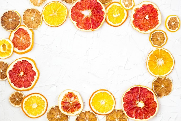 Border of dried slices of various citrus fruits on white frame background, orange lemon grapefruit with copyspace