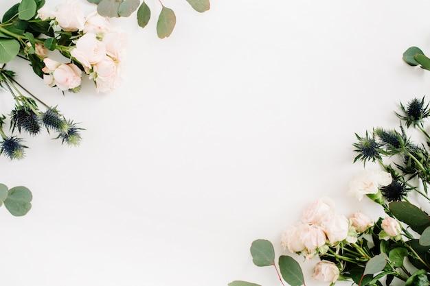 Пограничная рамка из цветов бежевой розы, цветка эрингиума, веток эвкалипта на белом