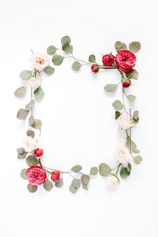 빨간색과 베이지 색 장미 꽃 봉오리와 흰색에 고립 된 유칼립투스 가지 테두리 프레임