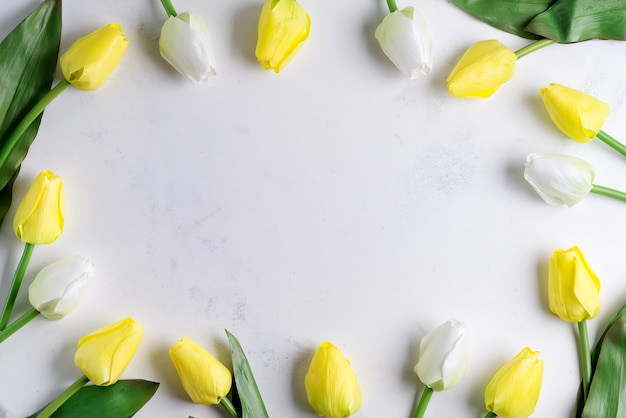 Border frame with white and yellow tulips on white marble background, copy space