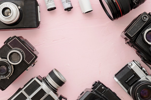 Border from cameras and film on pink background