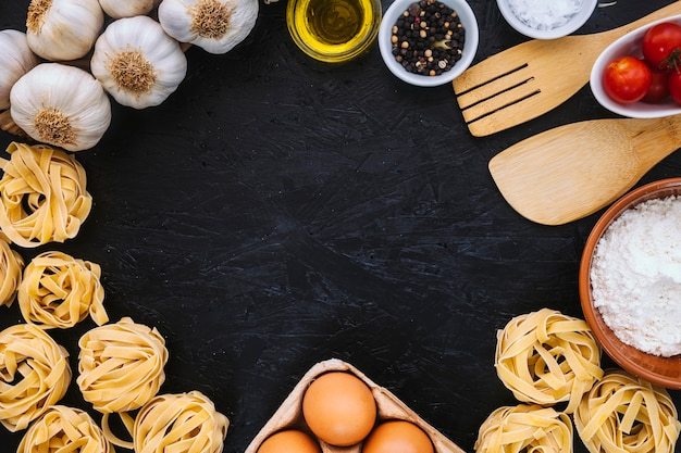 Border from spatulas and pasta ingredients