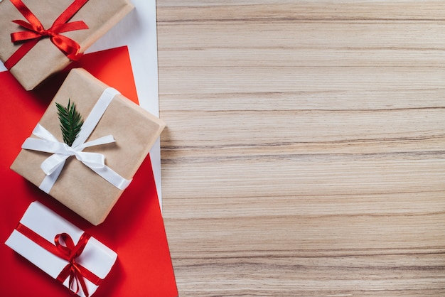Border of gift boxes wrapped in craft and white paper and decorated with satin ribbons