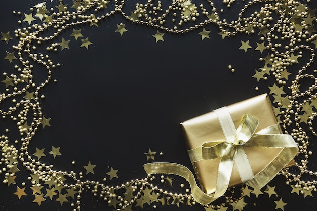 Border of luxury golden gift box on black background christmas present flat lay top view. xmas.