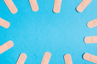 Border made with adhesive bandages on blue background