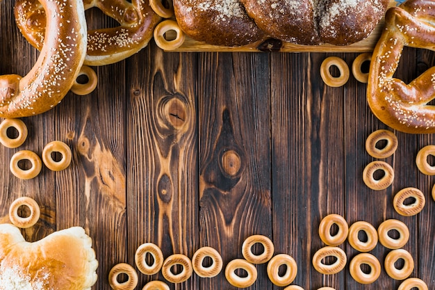 Border made with freshly baked plaited loaf, pretzels and bagels on the wooden background