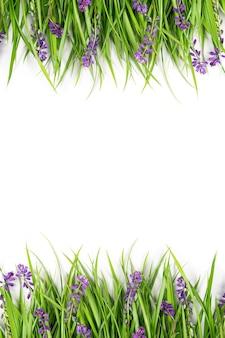 흰색 바탕에 푸른 잔디와 보라색 꽃으로 만든 테두리. 개념 봄 또는 여름 배경입니다. 디자인, 인사말 카드, 초대장, 엽서를 위한 템플릿 평면 위치 평면도 복사 공간.