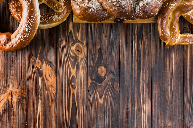 Border made with plaited loaf and pretzels on the wooden background