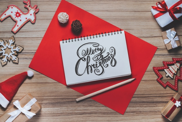 Border of new year decorations and gifts on wooden background with merry christmas wishes written with calligraphic font at the opened notebook