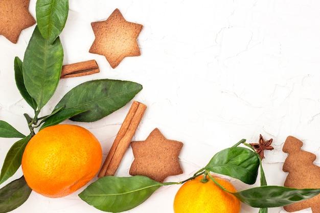 コピースペースと白い背景の上のスパイスとマンダリンとクリスマスの星のクッキーの境界線。上面図