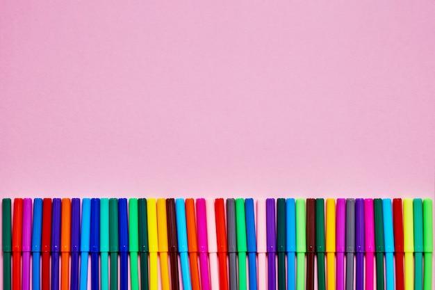 Граница цветных фломастеров на розовом фоне с местом для текста.