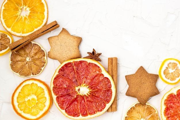 コピースペースと白い背景の上の様々な柑橘系の果物のジンジャーブレッドとスパイスの乾燥スライスの境界線。クリスマスフレーム