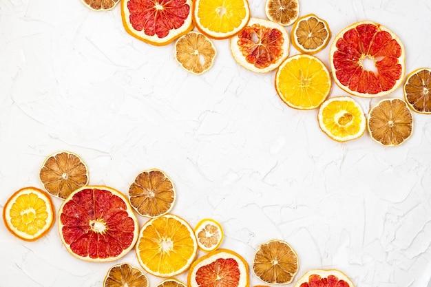 흰색 바탕에 다양한 감귤류의 말린 조각 테두리. copyspace와 많은 오렌지 레몬 자몽