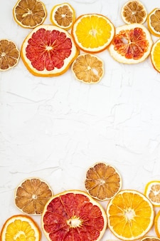白い背景の上の様々な柑橘系の果物の乾燥スライスの境界線。コピースペースのある多くのオレンジレモングレープフルーツ