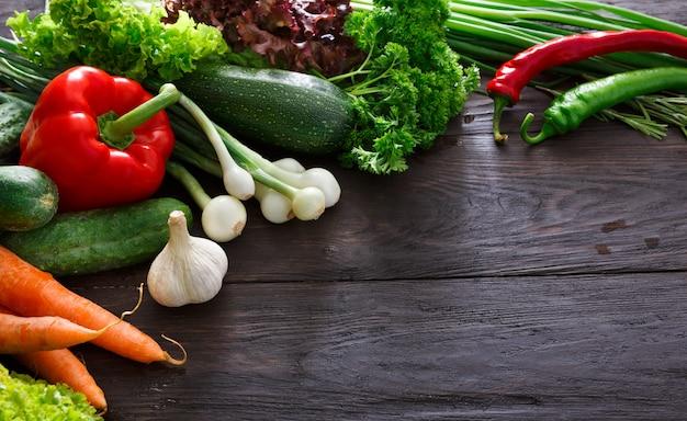 コピースペースを持つ木製の背景での新鮮野菜の境界線
