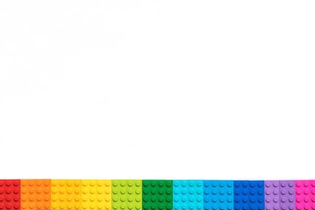 흰색 바탕에 여러 가지 빛깔의 plastick 생성자 벽돌의 테두리입니다. 인기있는 장난감.