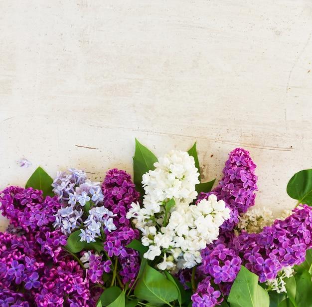 白い木製の背景に新鮮なライラックの花と緑の葉の境界線