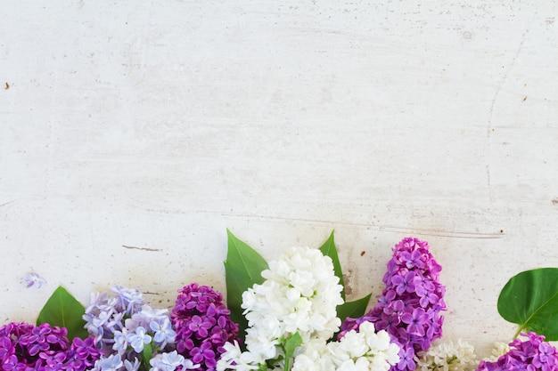 コピースペースと白い木製の背景に新鮮なライラックの花の境界線
